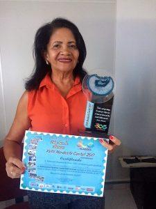 Maria Moura apesenta o Certificado e o troféu.